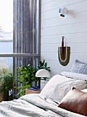 Bedroom with white painted wooden paneling and glazing