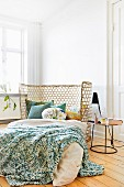 Semicircular cane headboard, knitted blankets and various scatter cushions on double bed
