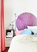 Runder lilafarbener Wandteppich an Bettkopfende