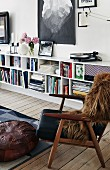 Brown fur blanket on retro armchair in front of books in sideboard