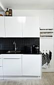 weiße Küche mit schwarzer Arbeitsplatte und Spritzschutz