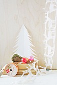 White hand-made paper garland of reindeer next to paper Christmas tree and toadstool ornaments in cardboard box