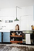 Vintage counter and board floor in kitchen with white-tiled wall