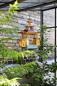 Candle in vintage birdcage used as lantern and foliage plants against brick façade