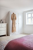 Dress hung on door of fitted wardrobe under sloping ceiling in bedroom