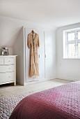 Kleid hängt am Einbauschrank unter der Schräge im Schlafzimmer