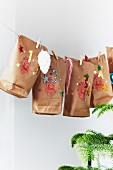 Advent calendar hand-made from decorated paper bags hung from string