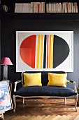 Antique sofa with yellow scatter cushions below framed modern artwork