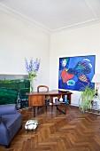 Retro Schreibtisch und moderne Gemälde in Wohnbereich mit Eichenparkett