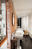 Rustic brick wall and vintage pedestal sinks in renovated bathroom