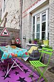 Bunte Gartenmöbel und Straßenschilder in einem Innenhof