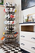 Collection of colourful mugs on old bottle-drying rack