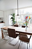 Dining table and various chairs in front of glass wall in kitchen