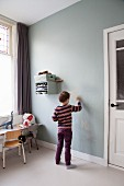 Boy drawing on wall
