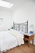 Black metal bed and wooden bedside cabinet in pale bedroom