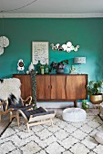 Ornaments on retro sideboard against green wall in comfortable living area
