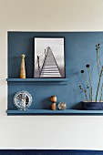 Blue rectangle on wall with ornaments on narrow blue shelves