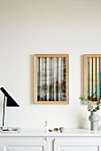 Two abstract artworks in wooden frames above sideboard