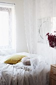 Romantic white lace curtain over bed with blankets and scatter cushions