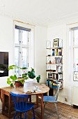 Houseplants on drop-leaf wooden table and bookcase in corner of room