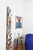 Bar stool used as bedside table between postcard rack and framed picture on wall