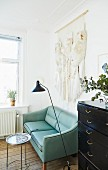 Pale wall hanging above turquoise two-seater sofa