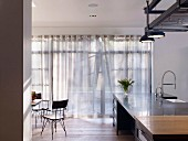 Light falling through curtains into modern kitchen with island counter
