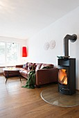 Lit fire in stove next to brown leather sofa