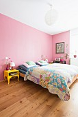 Pink walls and yellow bedside table in colourful bedroom