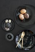 Goldfarbene Ostereier auf schwarzem Teller