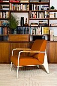 Brown armchair in front of retro-style veneer shelving
