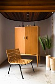 Easy chair with woven seat and wooden retro cabinet in semicircular room