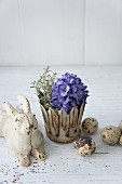 Easter bunny next to blue hyacinth and thyme in metal crown