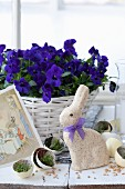 Easter bunny amongst egg halves, newspaper and cress