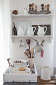 Alte Küchenutensilien in einem Wandregal und Holztablett