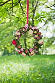 Wreath of flowers hung from branch in summer meadow
