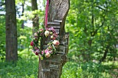Wreath of flowers hung on board with small signs in woodland
