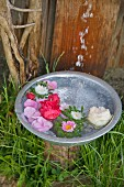 Water pouring into bowl of floating flowers