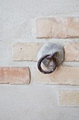 Rustic iron ring attached to concrete and brick wall