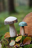 Two wooden toadstools, moss, leaves and acorns in woods