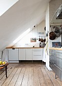 Kitchen with various fronts under sloping ceiling