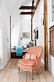 Salmon-pink Baroque armchair in entrance to bedroom with wood-beamed ceiling