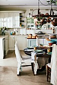 Dining table and chairs with rustic linen loose covers in country-house kitchen