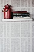 Red milk can and books on floating shelf on wall papered with book pages