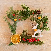 Square frame of fir twigs and decorations on wooden surface