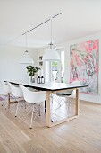 Shell chairs around modern dining table in front of abstract painting