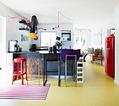 Various bar stools in colourful open-plan kitchen with yellow floor