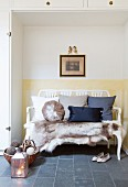 Fur rug and scatter cushions on wooden couch in niche surrounded by fitted cupboards
