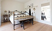 Rustic wooden bench at foot of old metal bed in bedroom