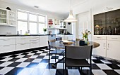 Round table on black and white chequered floor in white fitted kitchen